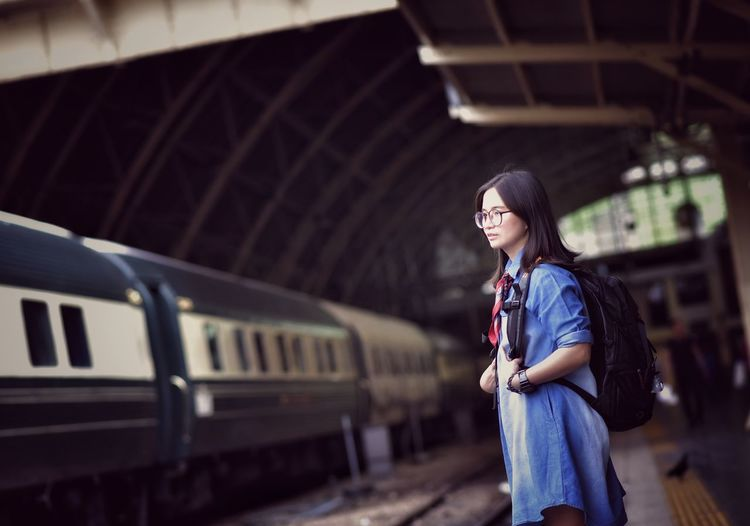 Side view of woman standing by train at railroad station