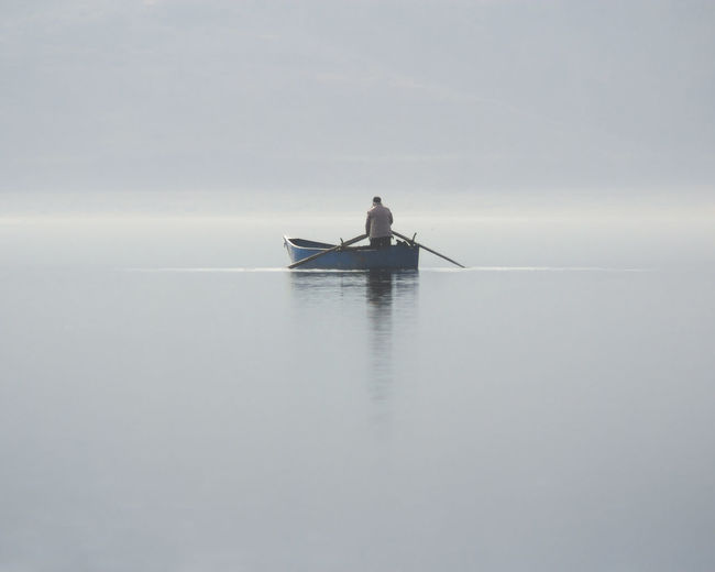 Man Sailing On Sea Against Sky