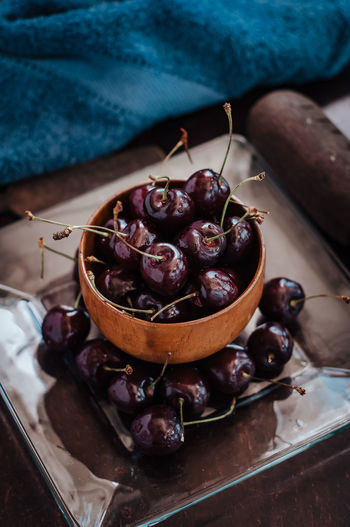 Close-up of cherry fruits in a wooden bowl on table