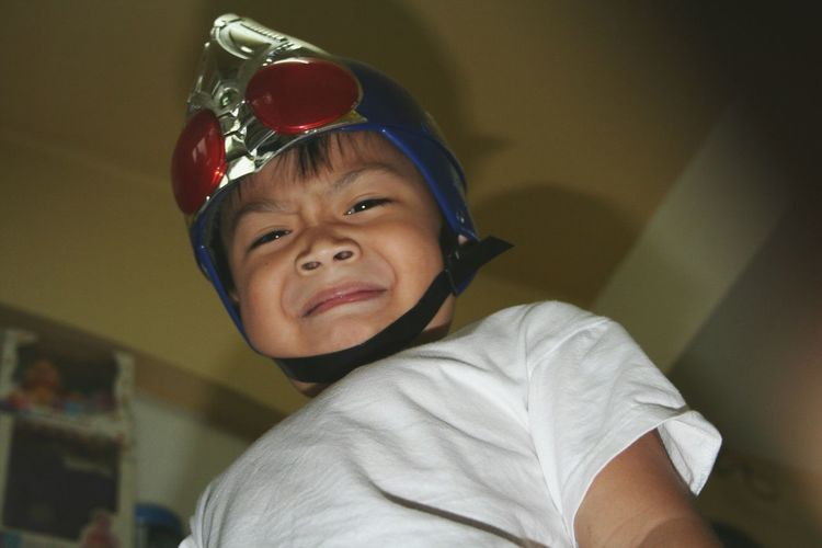 Low angle portrait of boy wearing helmet at home