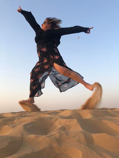 Low angle view of woman jumping on sand at desert against sky