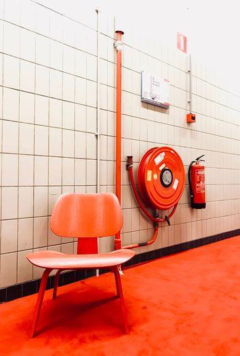 Orange chair on floor against tiled wall