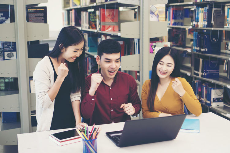 Students With Clenched Fists While Looking At Laptop On Table