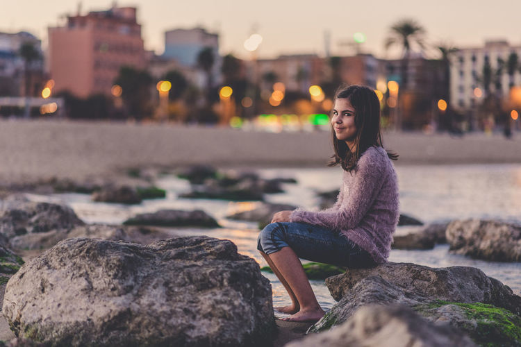 Portrait of young woman sitting on rock