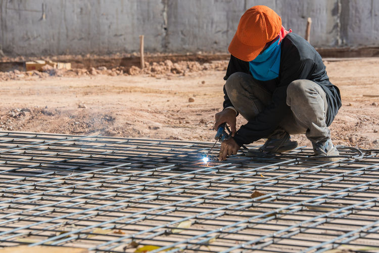 Full Length Of Worker Couching On Metal Grate While Welding