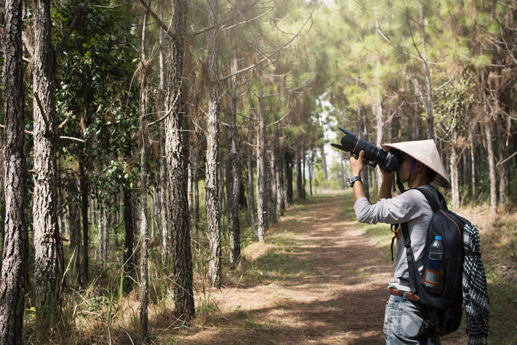 Side View Of Man Photographing While Standing In Forest