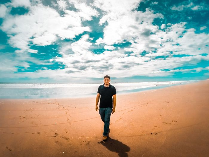 Full length of man standing on beach against sky