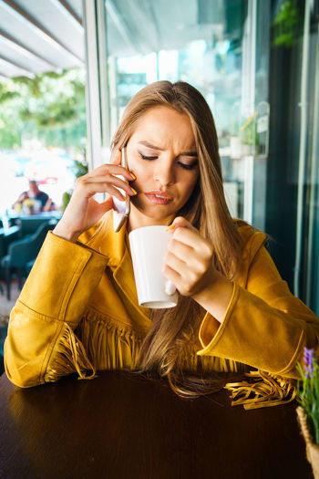 Young woman using mobile phone while sitting in cafe