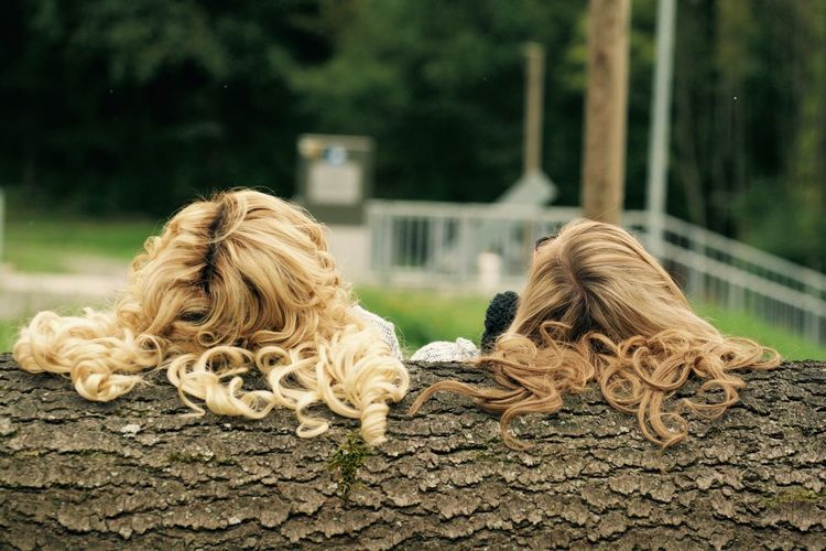 Rear view of girls with long hair resting on log