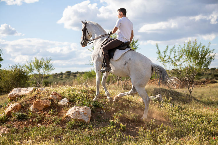 Men riding horse on field against sky