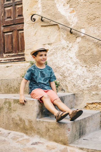 Full length of cute boy wearing hat sitting on steps