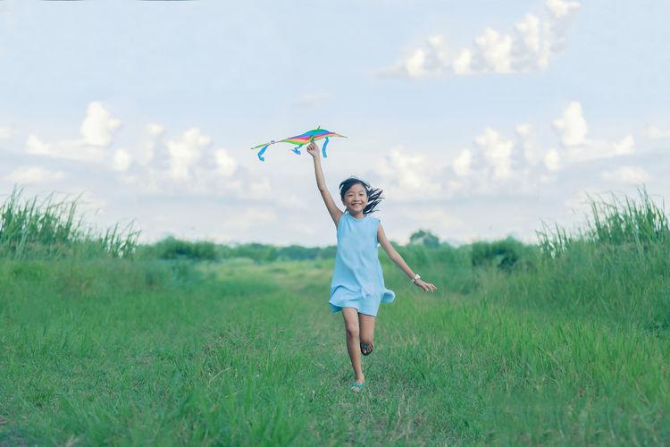 Full length of happy girl holding kite while running on grassy field against sky
