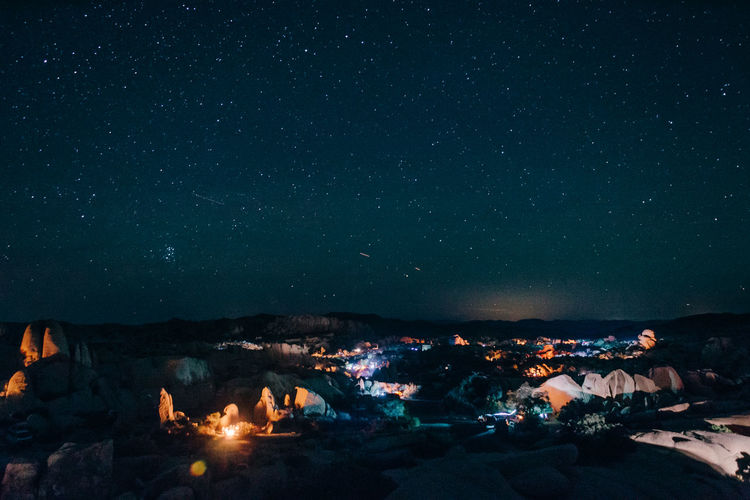 Illuminated camping grounds against sky at night