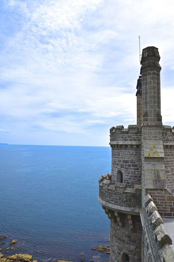 View of tower by sea against sky