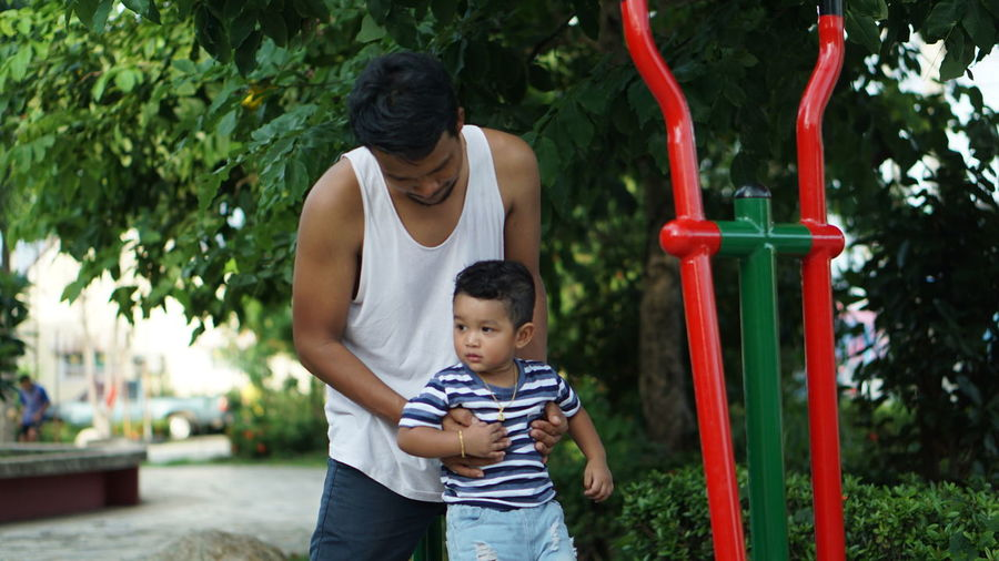 Father and son playing in park against trees