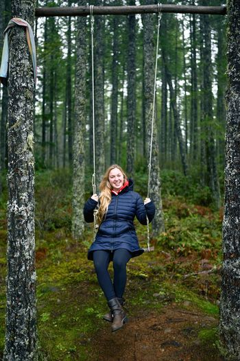 Portrait of smiling young woman swinging against trees in forest