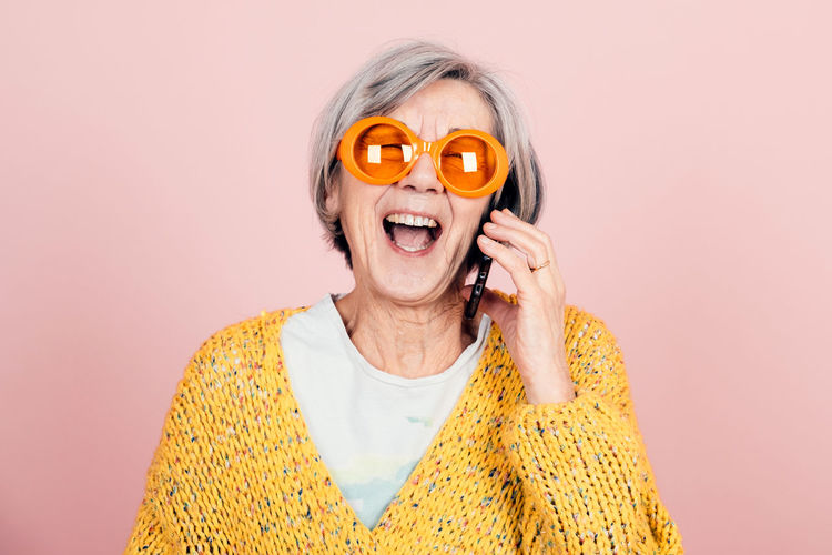 Happy young style elderly grandma with orange sunglasses and modern looking laughing on the phone