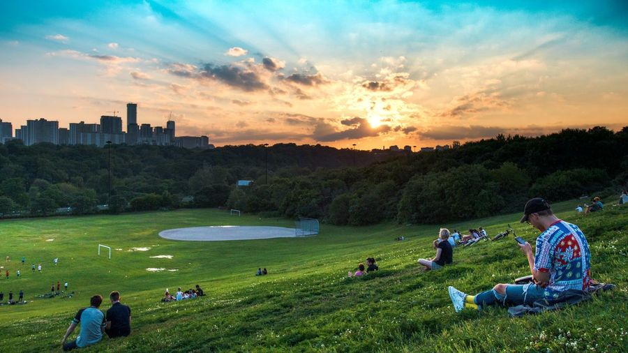 People sitting on golf course against sky during sunset