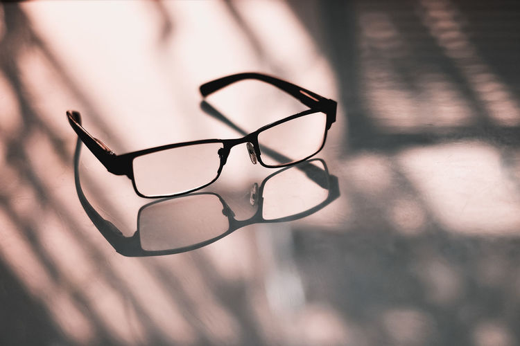 Eye Sight Vision Reading Glasses Optometrist Focus On Foreground Close-up No People Eyeglasses  Nature Glasses Day Outdoors Selective Focus Glass - Material Pattern Window Transparent Silhouette Plant Single Object Still Life Black Color Personal Accessory Glasses Eyeglasses  Sunlight Shadow Table