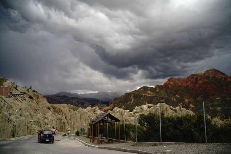 Cars on road by mountains against storm clouds