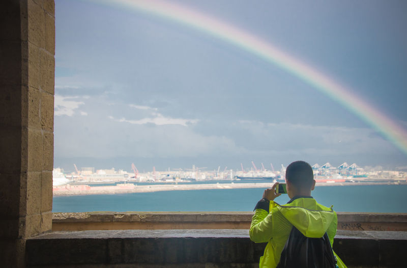 Rear view of man photographing standing by sea against rainbow in sky