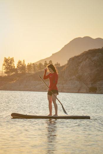 Full length of senior woman in lake against sky during sunset