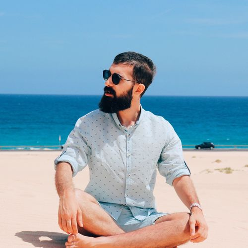 Young Man Sitting At Beach During Sunny Day