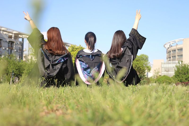 Rear View Of Friends Wearing Graduation Gown While Sitting On Grass