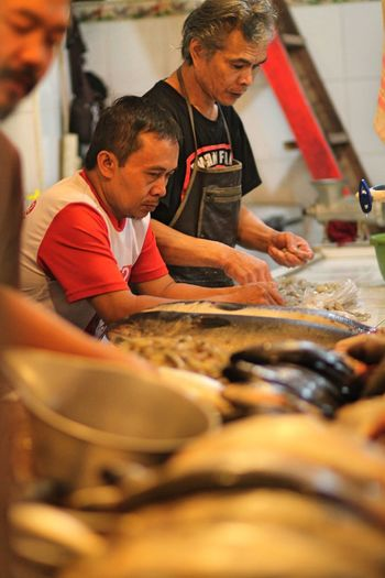 Chefs Making Seafood In Commercial Kitchen