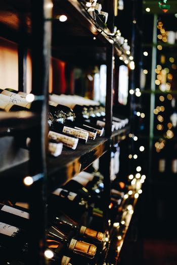 Wine bottles arranged on illuminated shelf during christmas
