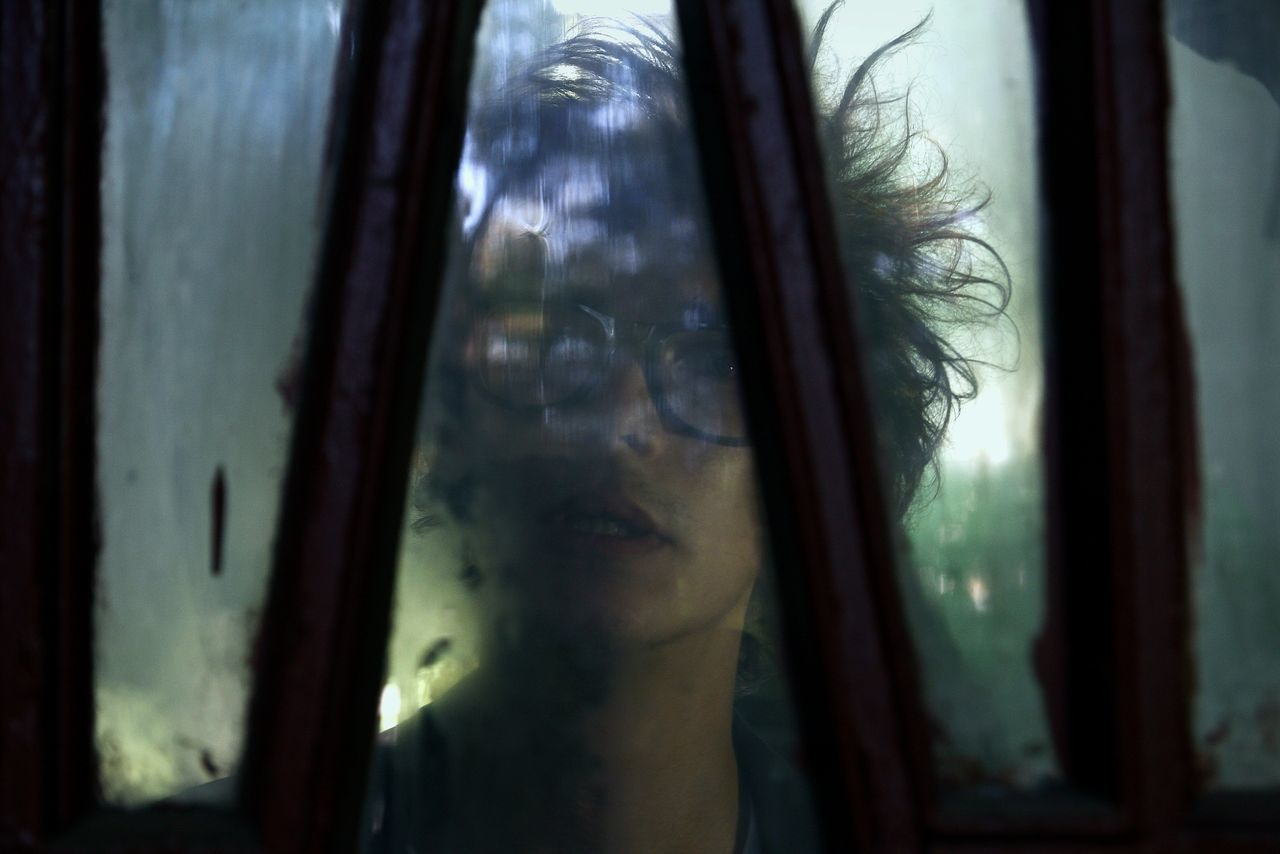 CLOSE-UP OF WOMAN SEEN THROUGH WINDOW