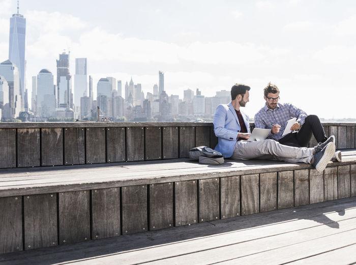 Full length of man sitting on mobile phone in city against sky