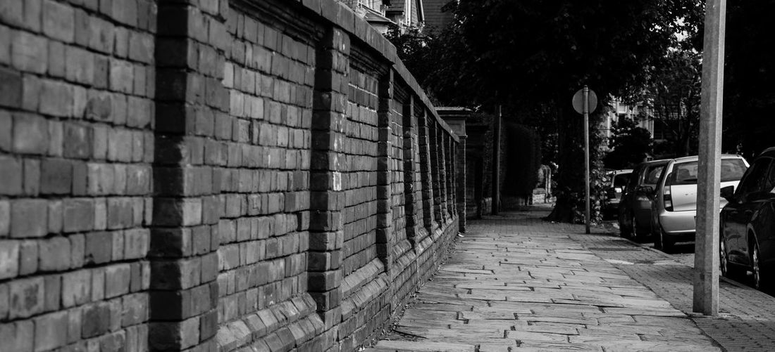 Architecture Brick Wall Built Structure Cars City City Life Crooked Diminishing Perspective Footpath No People Outdoors Pavement The Way Forward Vanishing Point