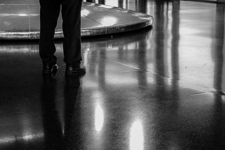 Low section of person standing on wet floor