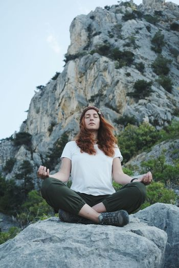 Full length of woman sitting on rock