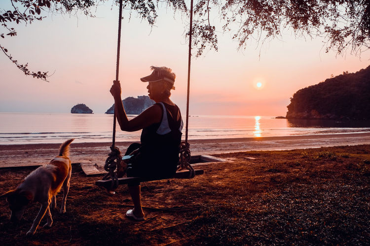 Side view of senior woman sitting on swing at beach against sky during sunset