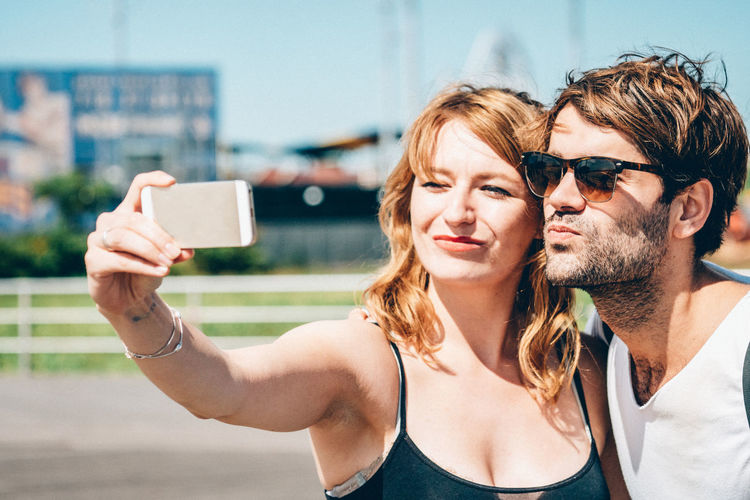 Happy friends clicking selfie on smart phone while standing outdoors
