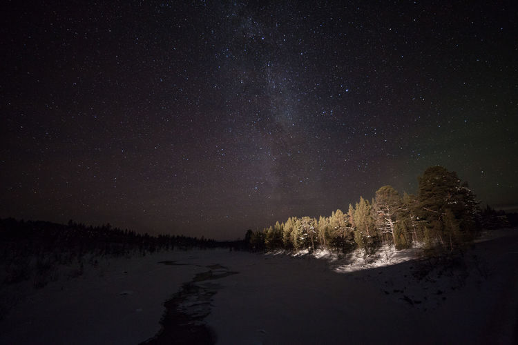 Stream on snow field against milky way