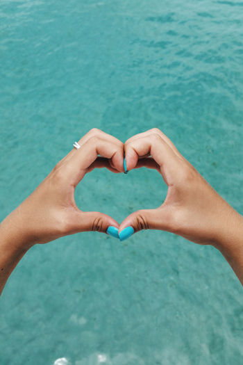 Close-up of hands holding heart shape against blue water