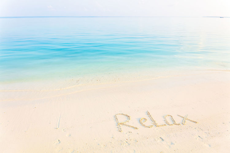 The Word Relax Written in the Sand on a Beach with morning sea background Water Sea Beach Land Sand Text Western Script Communication Tranquil Scene Tranquility Scenics - Nature Horizon Over Water Beauty In Nature Nature Horizon Idyllic No People Sky Day Positive Emotion Outdoors Message