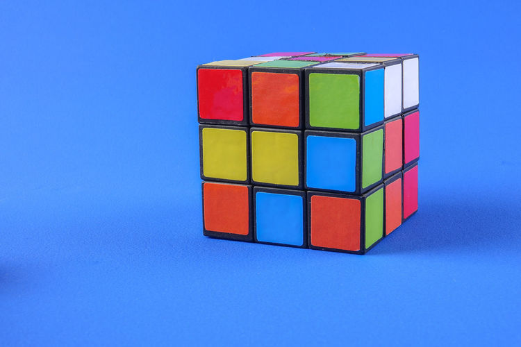 RUBIK'S CUBE , CREATIVITY TOY Creativity Rubik Cube Blue Blue Background Close-up Colored Background Copy Space Cube Shape Cut Out Design Geometric Shape Indoors  Intelligence Large Group Of Objects Multi Colored No People Rubik Shape Stack Still Life Studio Shot Toy Toy Block Wood - Material