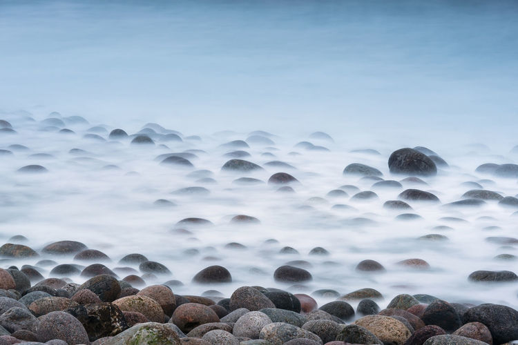 Long exposure of surf breaking on large boulders on the shore