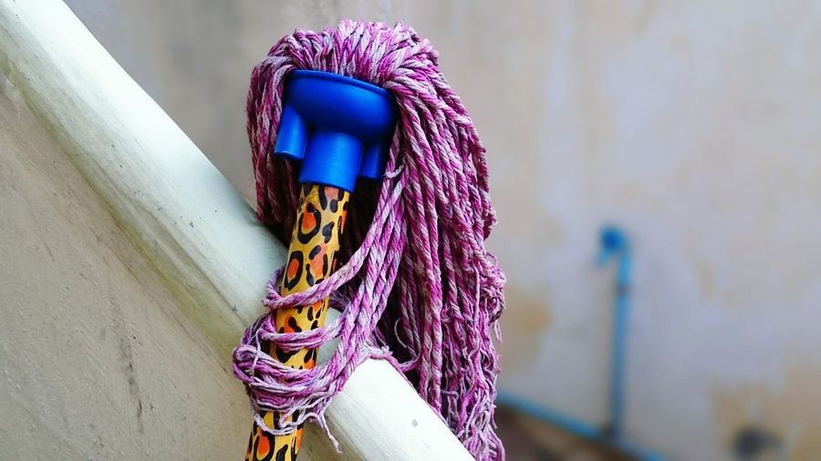 Close-up of cleaning mop by railing