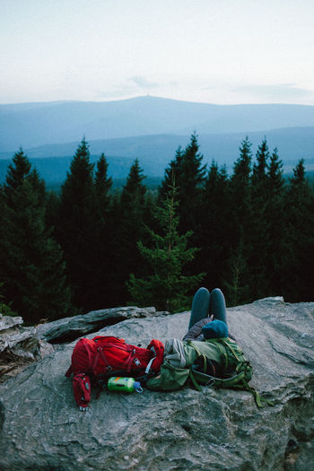 High angle view of person resting on mountain against sky in forest
