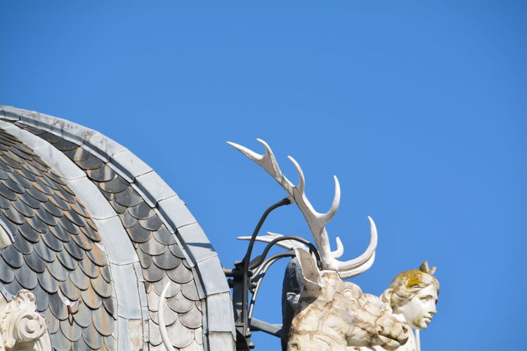 Low Angle View Of Sculptures On Roof Against Clear Sky