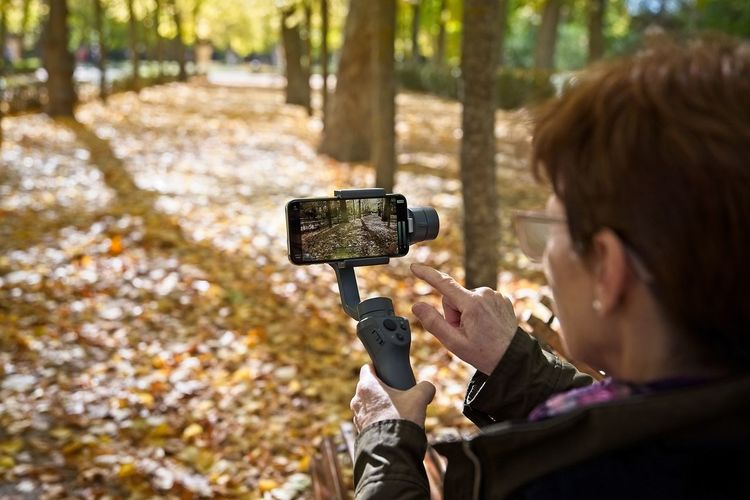 Senior woman touches her smartphone put on a gimbal to record video in a park in autumn Technology Headshot One Person Photographing Holding Portrait Camera - Photographic Equipment Wireless Technology Communication Adult Camera Outdoors Rear View Forest Over The Shoulder View Nature Smart Phone Recording Video Photo Screen Mobile Phone Gimbal Senior Woman International Women's Day 2019