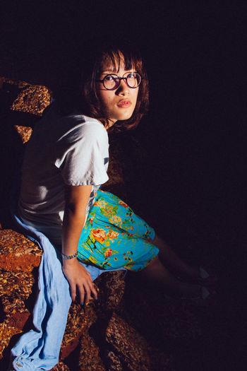 Full length of woman sitting on sofa in darkroom