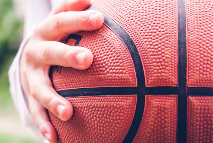 Close-up of hand holding ball little child hand holding a basketball ball sensory connection concept
