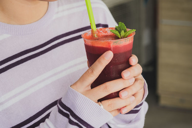 Midsection of woman holding beetroot smoothie