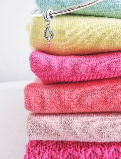 Close-up of metal jewelry on stacked clothes